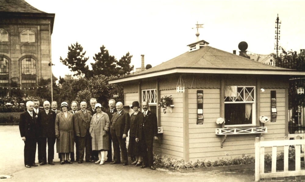 """Für heutige Verhältnisse unglaublich: Rund 100.000 (!) Besucher sahen im Sommer 1930 die """"Deutsche Rosenschau"""" in der Orangerie. Hier die Geschäftsstelle der Ausstellung mit den Organisatoren; im Hintergrund das nördliche Orangeriegebäude, das """"Orangenhaus"""". (Foto: MRV)"""