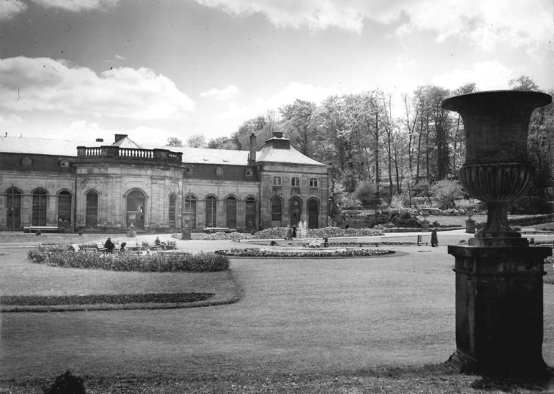 """1956 begannen die Sanierung des """"Lorbeerhauses"""" und sein Ausbau als """"Orangerie-Konzertcafé"""". Diese Aufnahme zeigt nicht nur sehr deutlich die seit dem Krieg vernagelten Fenster des Gebäudes, sondern auch sehr deutlich den bereits beräumten Platz des abgebrochenen südlichen Treibhauses. Bis heute ist es unverständlich, wie rabiat die Gothaer Stadtväter mit der einmaligen historischen Bausubstanz umgingen und vieles unwiederbringlich zerstörten. (Foto: Bundesarchiv)"""
