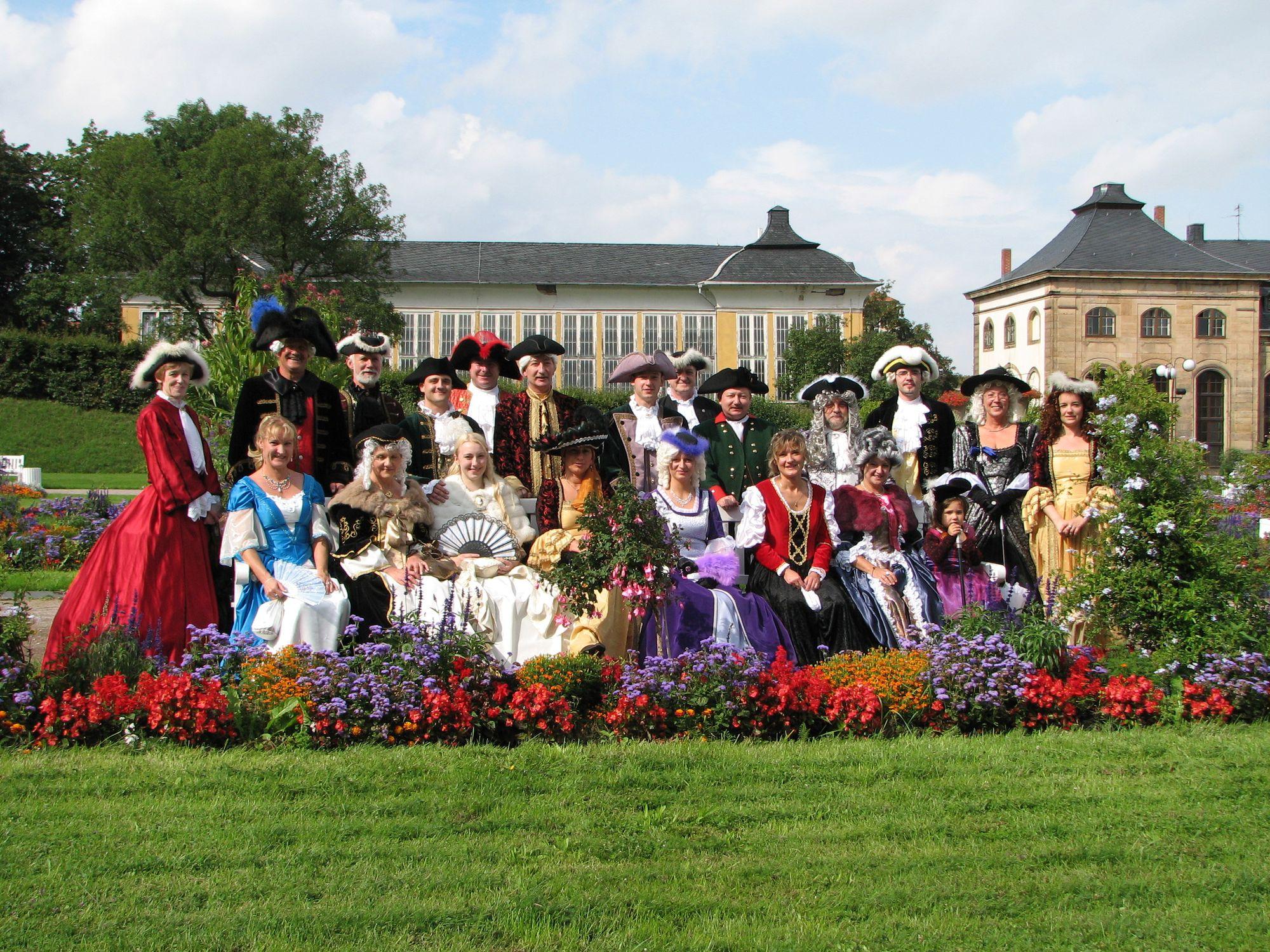 """Farbenprächtiges Kostümspektakel zum VI. Gothaer Barockfest: ein Teil der Hofgesellschaft Herzog Friedrichs III. von Sachsen-Gotha-Altenburg vor dem nördlichen Treibhaus und dem """"Orangenhaus"""". (Foto: Cramer)"""