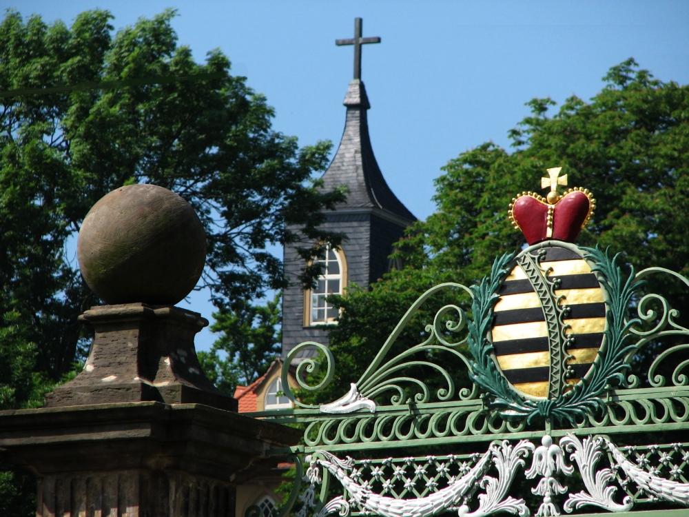 """Detailansicht des Portals mit sächsischem Rautenkranzwappen und Pfeilerbekrönung vor dem Hintergrund des Turmes des neogotischen """"Teeschlösschens"""", das sich südwestlich oberhalb der Gartenanlage erhebt. (Foto: Cramer)"""