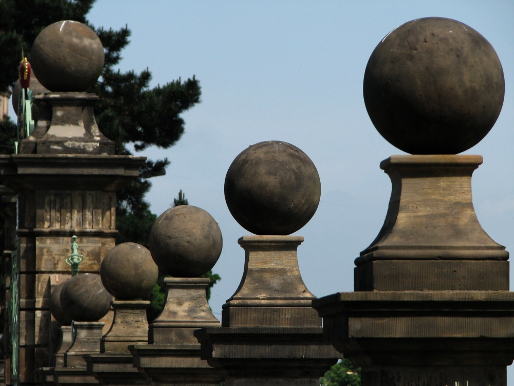 Ursprünglich wurden die Pfeiler des Portals und des Zaunes der Orangerie von steinernen Granatäpfeln gekrönt. Nach dem Tode Herzog Friedrichs III. im Jahre 1772 ließ sein Sohn Ernst II. diese jedoch entfernen und durch die schlichteren Kugeln ersetzen, die heute noch zu sehen sind. (Foto: Cramer)